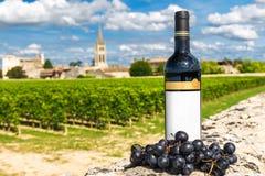 Flasche Rotwein vor dem hintergrund der Weinberge von Saint Emilion, Bordeaux, Frankreich lizenzfreie stockbilder