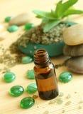 Flasche Schmieröl, Badesalz und Steine Stockfotos