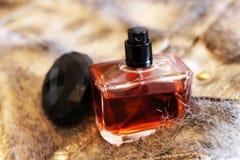 Flasche Schweinskopfsülzenparfüm auf einem Pelz stockfotos