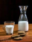 Flasche und Glas Milch mit Plätzchen Stockbild