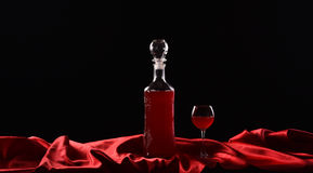 Flasche und Glas mit Rotwein auf schwarzem Hintergrund mit rotem Stoff, Satingewebe, Seide Lizenzfreie Stockfotos