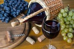 Flasche und Glas mit Rotwein, Weintrauben und Korkenzieher lizenzfreie stockfotos