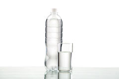 Flasche und Glas mit Wasser auf weißem Hintergrund Lizenzfreie Stockfotos
