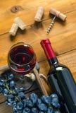 Flasche und Glas Rotwein auf hölzernem Hintergrund lizenzfreie stockbilder