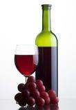 Flasche und Glas Rotwein mit Trauben Stockfotos