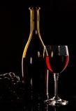Flasche und Glas Weintrauben auf schwarzem Hintergrund stockbilder