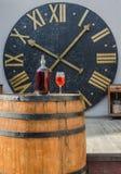 Flasche und Glas Wein auf einem Fass auf dem Hintergrund der Uhr Lizenzfreie Stockbilder