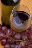 Flasche und Glas Wein mit Trauben auf Holz lizenzfreies stockbild