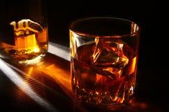 Flasche und Glas Whisky oder Bourbon mit Eis auf schwarzer Steintabelle Lizenzfreie Stockbilder