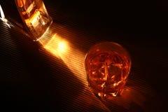 Flasche und Glas Whisky oder Bourbon mit Eis auf schwarzer Steintabelle Lizenzfreie Stockfotografie