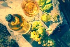 Flasche und volles Glas Weißwein über Weinberghintergrund Wi Stockbild