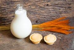 Flasche von Milch und von Minitortenapfel auf altem Holz Lizenzfreies Stockfoto