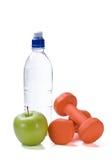 Flasche Wasser mit Eignunggewichten und -apfel stockfotografie