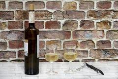Flasche Wein mit zwei Gläsern des Weißweins und des Korkenziehers stockbild