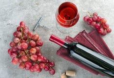 Flasche, Weinglas, Trauben und Korkenzieher auf grauer Tabelle lizenzfreies stockfoto