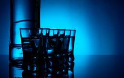 Flasche Wodka mit vielen Gläsern beleuchtete mit blauer Hintergrundbeleuchtung stockfotografie