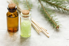 Flaschen ätherisches Öl und Tannenzweige für Aromatherapie und Badekurort auf weißem Tabellenhintergrund Lizenzfreie Stockfotografie