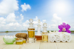 Flaschen aromatische Öle mit Kerzen, rosa Orchidee, Steinen und weißem Tuch auf Bretterboden auf unscharfem See mit bewölktem Him stockbilder