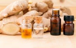 Flaschen des Ingweröls und des Ingwers auf hölzernem Hintergrund Stockfotografie