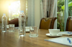 Flaschen des Wassers und des Tasse Kaffees auf Holztisch in der Konferenz Lizenzfreie Stockfotografie
