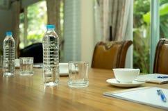 Flaschen des Wassers und des Tasse Kaffees auf Holztisch in der Konferenz Lizenzfreie Stockbilder