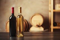 Flaschen köstlicher Wein und unscharfe Fässer lizenzfreie stockbilder