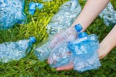 Flaschen Mineralwasser in der Hand der Frau, Abfall von Umwelt Lizenzfreie Stockfotografie