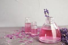 Flaschen mit aromatischem Lavendelöl auf grauer Tabelle stockfotos
