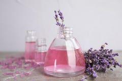 Flaschen mit aromatischem Lavendelöl auf grauer Tabelle stockbilder