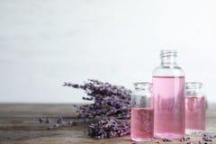 Flaschen mit aromatischem Lavendelöl auf Holztisch stockbild