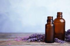 Flaschen mit aromatischem Lavendelöl auf Holztisch stockfoto