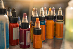 Flaschen mit den verschiedenen Tinten, die auf Schreibtisch finden Stockfotografie
