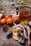 Flaschen mit Emulsion, Steinen, trockenen Kräutern und hölzernen Details Geheimnisvolles, geheimes, Weissagungs- und wiccakonzept stockfotografie