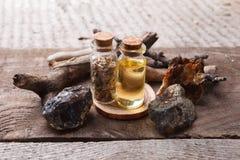 Flaschen mit Emulsion, Steinen und hölzernen Details Geheimnisvolles, geheimes, Weissagungs- und wiccakonzept Mystischer, alter A stockbilder