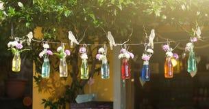 Flaschen mit farbigem Wasser und den Blumen, die an einer Schnur auf Sommerstraßenhintergrund hängen lizenzfreie stockfotografie