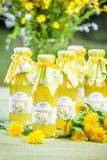 Flaschen mit Löwenzahnblumensirup Lizenzfreie Stockfotos