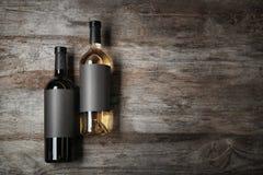 Flaschen mit leeren Aufklebern auf hölzernem Hintergrund stockfoto