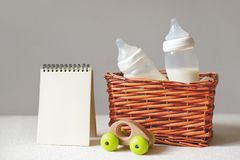 Flaschen mit Muttermilch für Baby in einem Strohkorb- und -papiernotizbuch nahe ihm Freiexemplarraum stockfoto
