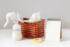 Flaschen mit Muttermilch für Baby in einem Strohkorb- und -papiernotizbuch nahe ihm Freiexemplarraum stockbild