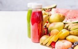 Flaschen mit roten Smoothies und Saftgetränken auf weißem Tabellenhintergrund mit Sommerfrüchten und Beeren, Vorderansicht Gesund lizenzfreie stockfotos