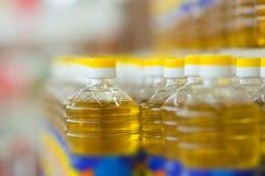 Flaschen mit Sonnenblumenöl auf Regalen im System Stockfotografie