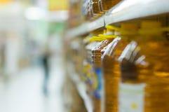 Flaschen mit Sonnenblumenöl auf Regalen im System Lizenzfreie Stockfotos