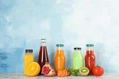 Flaschen mit verschiedenen Getränken und Bestandteile auf Tabelle lizenzfreies stockfoto