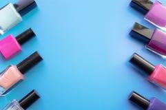 Flaschen Nagellack Eine Gruppe helle Nagellacke auf einem blauen Hintergrund Mit leerem Raum in der Mitte stockfotografie