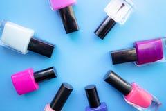 Flaschen Nagellack Eine Gruppe helle Nagellacke auf einem blauen Hintergrund Mit leerem Raum in der Mitte stockfotos