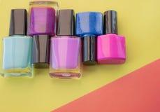 Flaschen Nagellack Eine Gruppe helle Nagellacke auf einem farbigen, gelben Hintergrund lizenzfreie stockfotografie