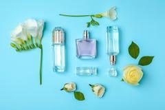 Flaschen Parfüm und Blumen auf Farbhintergrund stockfotos