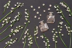 Flaschen Parfüm- und Maiglöckchenblumen auf schwarzem Hintergrund Parfümerie, Duft, kosmetisches Konzept Frühling oder Sommer lizenzfreie stockfotos