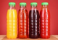 Flaschen Saft auf Rot stockbild