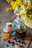 Flaschen Tinktur und trockene Kräuter, heilende Kräuter in der Holzkiste lizenzfreie stockbilder